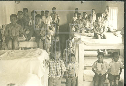 13.e.5-57.18 young males in contemporary attire in their dorm rooms at a boarding school- village of Gonogochi