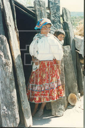 3.l-54.80 female and baby in rebozo beside removable plank door- near village of Wawatzerare
